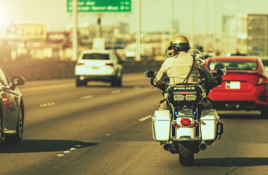 Caucasian Police Officer on a Motorcycle on a Highway
