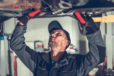 Caucasian Professional Car Mechanic Undercarriage Check