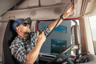 Caucasian Semi Truck Driver Talking by CB Radio