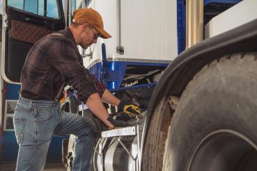 Caucasian Trucker Looking Inside Semi Truck Fuel Tank