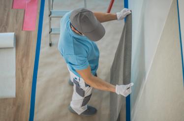 Caucasian Worker Applying Vinyl Wallpaper