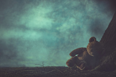Child Abuse Concept with Lost Teddy Bear in Dark Foggy Forest.