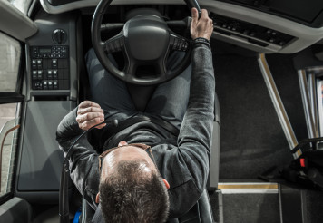 Coach Bus Driver Behind the Vehicle Talking to Vehicle Intercom Wheel Top View