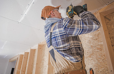 Construction Contractor Attaching Drywall Elements to the House Ceiling