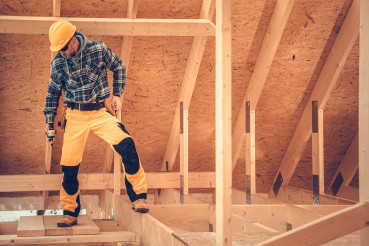 Construction Contractor Inside Newly Built Wooden House Skeleton