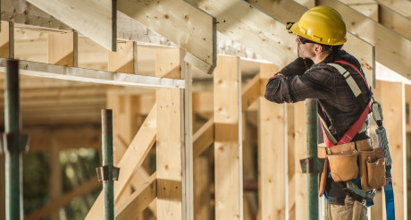Construction Worker and Newly Built Wooden Roof Frame