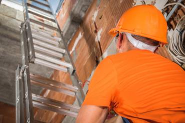 Construction Worker Going Upstairs Using Aluminium Ladder