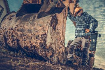 Construction Worker in Front of Excavator Bucket