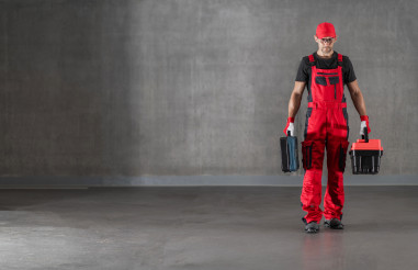 Construction Worker in Red Uniform Walking with Toolboxes in His Hands