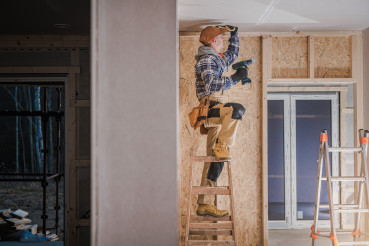 Construction Worker Installing Drywall Ceiling Elements