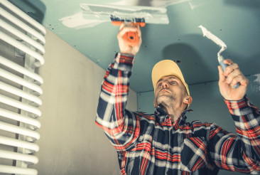 Construction Worker Patching Bathroom Ceiling
