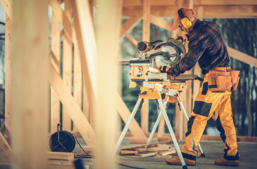 Construction Worker Using Large Powerful Circular Saw