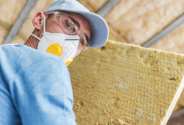 Contractor Worker with Piece of Mineral Wool Home Insulation Material