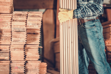 Contractor Worker with Wood Planks in Hand For Construction Project