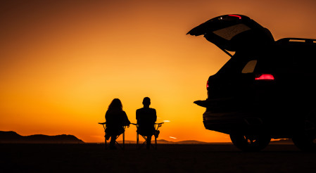 Couple Enjoying Scenic Sunset on a California Desert Seating Next to Their Vehicle