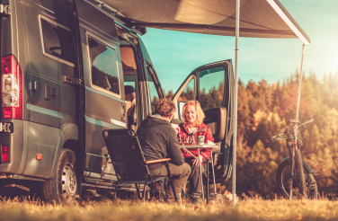 Couple Playing Chess Next to Their Camper Van RV