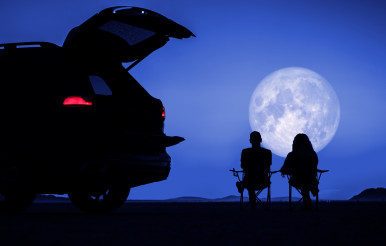 Couple Seating Next to Their Vehicle and Enjoying Full Moon Vista