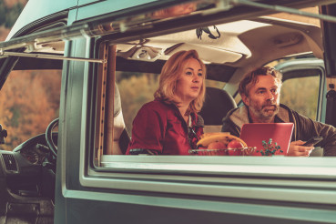 Couple Watching Exciting TV Game Inside Camper Van RV