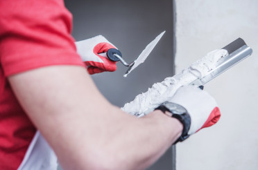 Construction Worker Applying Drywall Compound On Taping Knife.