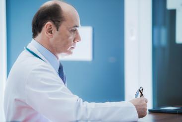Medical Doctor Sitting At Desk In Office.