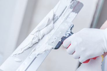 Close Up Of Professional Worker Patching Drywall.