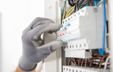 Electrician Testing Fuses In the Electric Box