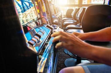 Gambler Playing Slot Machine Inside a Casino