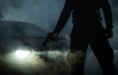 Gang Member with Handgun in Front of His Car During Night Hours
