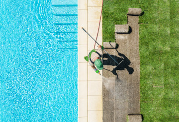 Gardener Finishing Lawn Around Swimming Pool