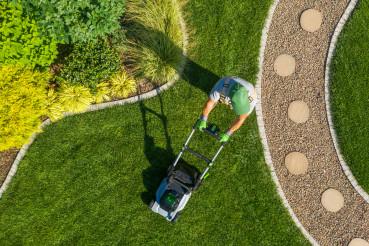 Gardener Mowing Backyard Garden Grass Aerial View.