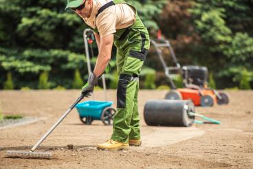 Gardener Performing Grass Seeding and Soil Preparation