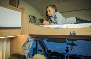 Girl Hanging on Bunk Camper Bed with Her Smartphone