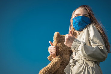 Girl in Face Mask Holding Large Teddy Bear