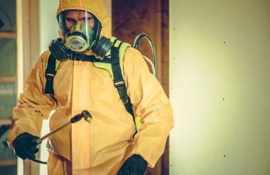 Hazmat Suit Worker Spraying Disinfection Liquid