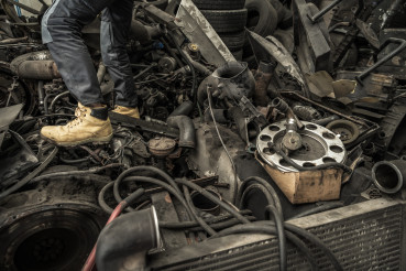 Hoarder Walking on a Pile of Automotive Waste and Used Parts
