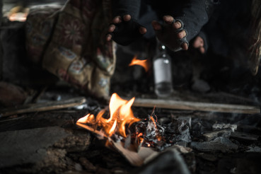 Homeless Men Heating Himself with Small Fire