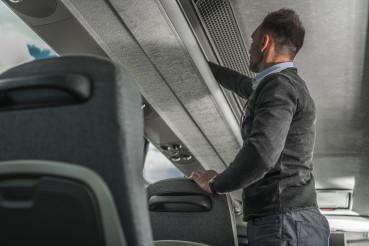 International Coach Bus Passenger Securing Luggage Inside Vehicle