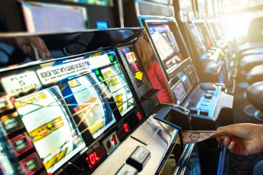 Las Vegas Slot Machine Player Inserting Banknote For Another Game