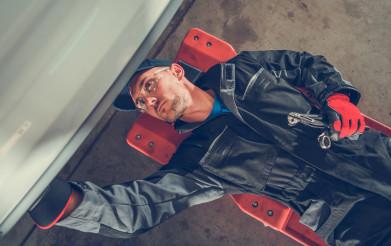 Man On Mechanics Creeper Fixing Undercarriage.