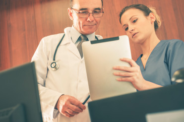 Nurse And Doctor Looking At Patient Medical Information.