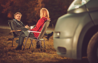 Men and Woman Chatting on a Campground Next to Camper Van