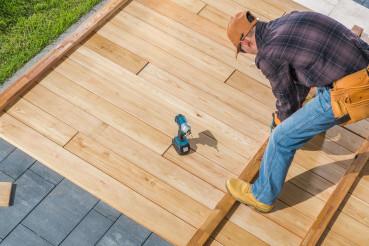 Men Building Wooden Deck on His Backyard
