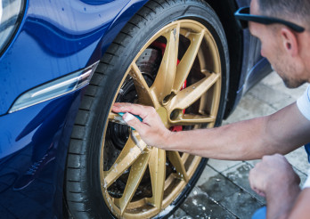 Men Cleaning Alloy Wheels of His Car