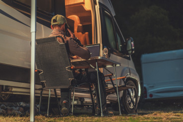 Men Making Business Phone Call While Camper Camping