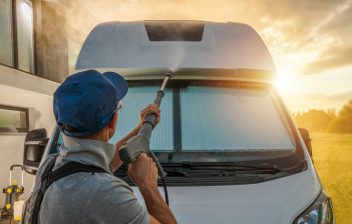 Men Pressure Washing His Camper Van RV During Scenic Sunset