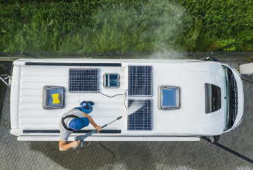 Men Pressure Washing RV Camper Van Roof Equipped with Solar Panels
