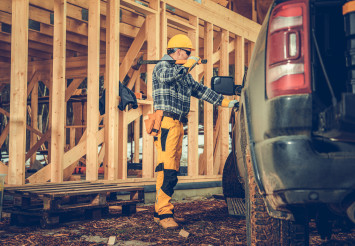 Contractor with Large Hammer and the Construction Site