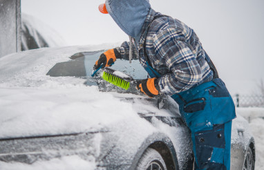 Men Removing Snow From His Vehicle and Deicing Windshield.