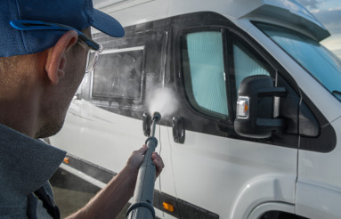 Men Washing RV Camper Van Using Pressure Washer