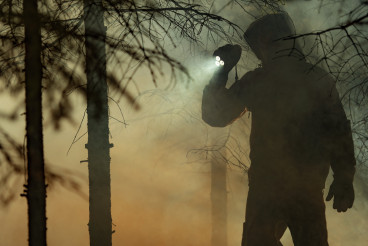 Men with Flashlight During Forest Wildfire Rescue Mission